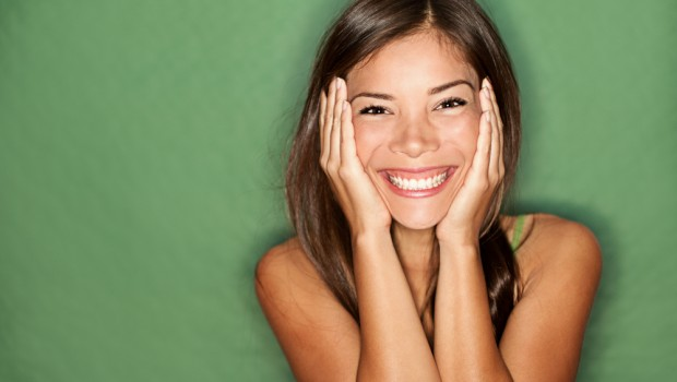Happy woman holding face on green background
