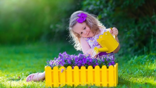 girl watering purple flowers